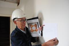 Roland Heini vor der Wand im künftigen Foyer des Dachgeschosses mit einem Entwurf des Gipsreliefs, das er darauf anbringen wird.