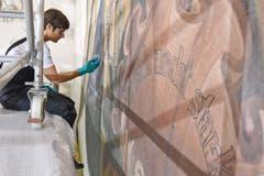 Mit einem Schwamm reinigt Vergolderin Jenny Schwarz ein Wandgemälde.
