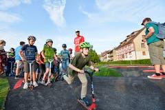 Die ersten Schulkinder testen mit Kickboard und ausgerüstet mit Helm den neuen Pumptrack.