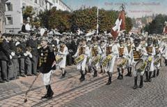 Tambouren vor 1914 auf dem Burggraben. Links am Strassenrand die Kadettenmusik, dahinter die Abzweigung der Glocken- in Richtung Brühlgasse mit dem Gebäude und dem Biergarten des Restaurants «Zur Harfe».