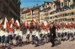 Eine Bubenklasse mit ihren Schulfahnen auf einer kolorierten Ansichtskarte um 1932.