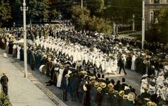 Der Kinderfest-Umzug um 1913: Die Mädchenklasse samt Blasmusik dahinter kommen aus dem Kantipärklein auf den Burggraben. Am rechten oberen Bildrand ist eine Ecke des Gebäudes der Kantonsschule am Burggraben zu erkennen.