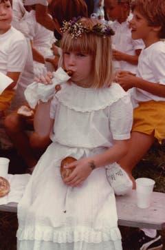 Zwischen Tradition und Erneuerung: 1983 lässt sich ein Mädchen im weissen Spitzenkleid seine Kinderfest-Bratwurst schmecken. (Bild: Stadtarchiv der Ortsbürgergemeinde St.Gallen/Sammlung Foto Gross)