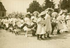 Eine frühe Foto-Ansichtskarte des Kinderfest. Das Bild ist um 1900 gelaufen und zeigt ganz in weisse Spitzen gekleidete Blumenmädchen im Anstieg zur Festwiese.