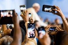 Überall knipsen die Handys. (Bild: Jean-Christophe Bott / Keystone)