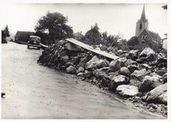 Steine türmen sich nach dem Unwetter auf der Staatsstrasse vor der Kirche. (Bild: Staatsarchiv SG)