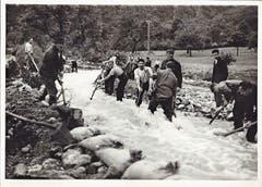 Die Zivilbevölkerung hilft mit Pickeln und Schaufeln, den Steinenbach von Steinen und Holz zu befreien. (Bild: Archiv Roger Urfer)