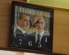 In der Metzgerei Muheim zeigt diese Uhr die Zeit an, hinterlegt mit einem Bild von Dimitri Medwedew und Vladimir Putin. (Bild: Urs Hanhart (Andermatt, 8. Juni 2018))