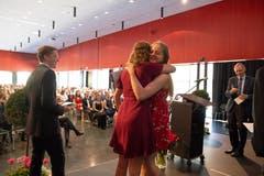Carole Waldvogel (links ) und Aline Pironato (zweitbeste und beste Matura) umarmen sich.Links freut sich Jan Wallimann (drittbeste Matura).