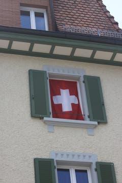 Die Schweizer Fahne als Vorhang im Fenster eines Hauses an der Gerbestrasse in der Lachen.