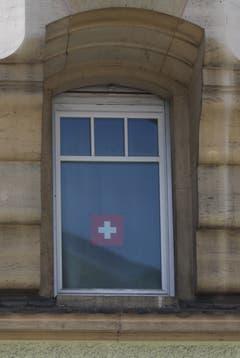 Die Intensität der Sympathie hängt nicht von der Grösse des Fahnentuchs ab: Schweizer Fähnli im Fenster eines Hauses an der Zürcher Strasse in der Lachen.