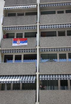 Farbtupfer an einer grauen Hausfassade an der Feldlistrasse: die serbische Flagge.