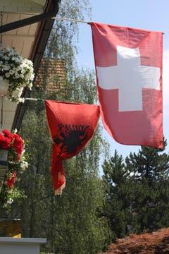 Viele Albanerinnen und Albaner fiebern an dieser WM mit der Schweizer Nati mit. Eine albanische und eine Schweizer Fahne in einem Garten an der Fürstenlandstrasse.