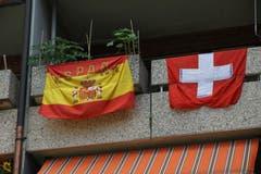 Spanisch-schweizerische Freundschaft auf einem Balkon an der Andreasstrasse in der Lachen. Dass die Schweizer Fahne das Werbeprodukt eines Bündner Bierbrauers ist, tut nichts zur Sache.