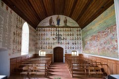 Auch über dem Eingang finden sich Namen und Wappen gefallener Habsburger. Im Bogenfeld oberhalb der Wappen die Gottesmutter Maria im Strahlenkranz mit dem Jesuskind auf dem Arm. Sie wird flankiert von Bischof Cyrill und Jakobus dem Älteren. (Bild: Boris Bürgisser, 18. Juni 2018)