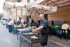 Vor der Trattoria Torremuzza wird der Fisch auf dem Grill zubereitet.