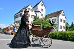 Kein Kinderwagen: die Drehorgelfrau kurbelt vor der Schlosskulisse Melodien.