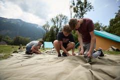 Philipp Bundi, Elias Arnold und Elias Brunner (von links) bauen ihr Zelt auf. (Bild: Jakob Ineichen, 7. Juli 2018)