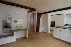 Grösser könnte der Kontrast kaum sein: rechts die moderne neue Küche, links der alte Ofen aus früherer Zeit.
