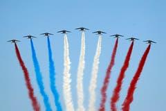Farbenfrohe Panne am französischen Nationalfeiertag: Einer der Kampfjets hatte rote statt blaue Farbe geladen. Anstelle der erwarteten Tricolore entstand so ein rot-blau-weiß-roter Streifen am Pariser Himmel. (Bild: AP Photo/Francois Mori)