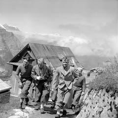 Andreas Heckmair, links, und Heinrich Harrer, Zweiter von rechts, laufen nach ihrem Aufstieg durch Grindelwald. (Bild: Keystone/ Photopress-Archiv/ Str)