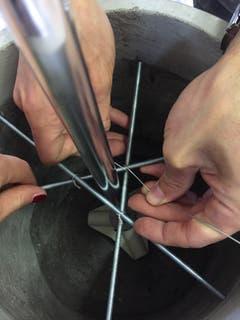 Anschliessend auf zwei unterschiedlichen Höhen je drei Stangen direkt am Rohr befestigen. Am besten überkreuzt man dafür die Stangen und umwickelt sie mit Draht so oft, bis alles fest hält. (Bild: Migros)
