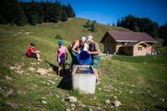 Köbi Alder und sein Sohn Ueli füllen einen versiegten Brunnen mit Wasser. (Bild: Benjamin Manser)