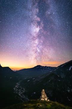 Auf dem Pass Diesrut (2428m) mit Blick auf die Greinaebene und dem mäandrierenden Fluss. Ein Steinmännchen bildet den passenden Vordergrund, während die Milchstrasse den Nachthimmel erhellt. (Bild: Adrian Steg)