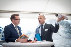 Regierungsrat Benedikt Würth hilft Markus Sauerbruch (rechts), Leiter der Stadler-Division Schweiz, beim Verpacken der Baupläne in eine Hülse für den Spatenstich.