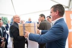 Stadler-Inhaber und Verwaltungsratspräsident Peter Spuhler überreicht die Baubewilligung in der Schachtel an HRS-CEO Martin Kull.