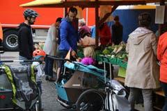 Mit Kind und Kegel an den Bauernmarkt: junge Väter und ihre Sprösslinge vor der Gemüse-Auslage.