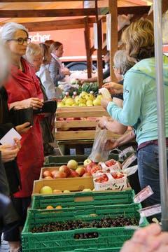 Kundinnen und Verkäuferinnen vor der Auslage mit Obst aus Lömmenschwil.