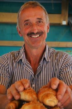 Bauernmarkt-Präsident Rolf Bischofberger vom Sunnehof bei Oberegg beigt Gipfeli auf.