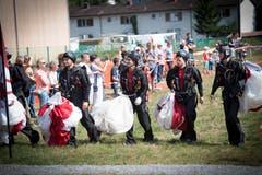 Fallschirmspringer tragen ihre zusammengerafften Fallschirme. (Bild: Ralph Ribi)