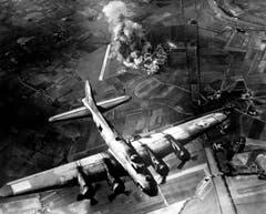 Eine B-17F beim Wegflug von einem deutschen Ziel: Da die Sichtbedingungen hervorragend sind, wurde das Flugzeugwerk neben der Flugpiste im Hintergrund von einem dicht konzentrierten Bombenhagel getroffen. (Bild: US Air Force)