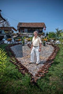 Martin Erni steht in seinem Garten inmitten eines Herzen, das aus alten Radschuhen erstellt worden ist. (Bild: Pius Amrein (21.8.2018))