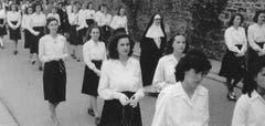 Mère Marie Hedwig mit feierlich gekleideten Schülerinnen.