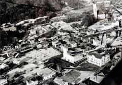 Blick aus dem von Pfarrer Oswald pilotierten Flugzeug mit Sicht auf die beiden Kirchen und das Schulhaus Grof.