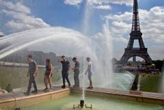 Erfrischung mit Aussicht: Beim Pariser Eiffelturm suchen Touristen nach einer Abkühlung. (Bild: Keystone)