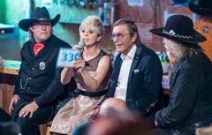 Die Moderatoren Linda Feller und Johnny Hill sitzen zwischen Cowboys.