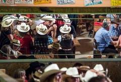 Die Spiegel an der Wand verdoppeln die ohnehin zahlreichen Cowboy-Hüte.