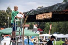 """Sven von den """"Heutröchner"""" befestigt die Plane des Pavillons."""