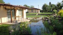 Vor dem Haus liegt ein kleiner Teich, dahinter befindet sich in einem separaten Gebäude die Garage.
