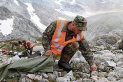 Im Einsatzgebiet «unter den Hüenerstöcken» sammelt ein Soldat Munitionsreste ein. (Bild: Philipp Zurfluh, Realp, 9. August 2018)