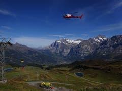 Helikopter mit rotem Kübel am Seil mit Grindelwald im Hintergrund. (Bild: Josef Müller (Männlichen, 11. September 2018))