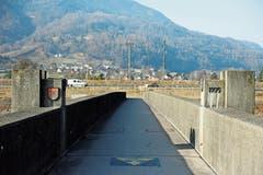 Ein symbolisches Tor in Flussmitte mit dem Baudatum und den Gemeindewappen markiert die Landesgrenze auf der kleinen Rheinbrücke. (Bild: Cornel Doswald)