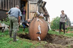 Vorsichtig wird die Kwewri mit dem Bagger etwa zwei Meter tief im Boden versenkt. (Bild: Bilder: Corinne Hanselmann)