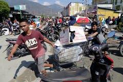 Aus dem zerstörten Einkaufszentrum werden Güter abtransportiert. (EPA/Must Irham)