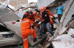 Bergung eines Opfers aus den Trümmerteilen eines zerstörten Gebäudes. (AP Photo/Tatan Syuflana)