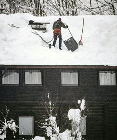 Ein Mann befreit ein Dach von der Schneelast, aufgenommen in Saalbach (Bild: APA / Keystone)